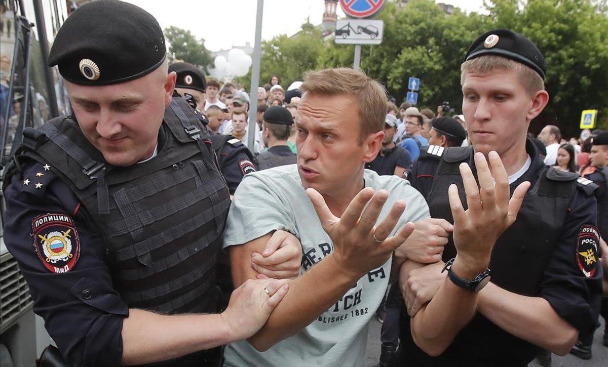Dos agentes detienen al líder opositor ruso Aléxei Navalny durante las protestas por la detención del periodista de investigación Ivan Golúnov, este miércoles, en Moscú.