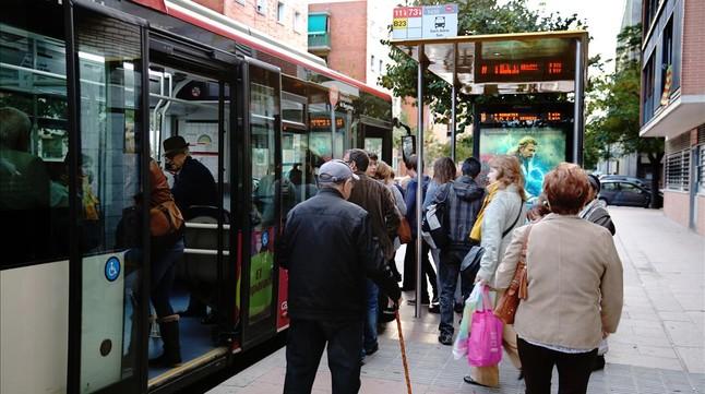 Un grupo de ciudadanos hacen cola en una parada de autobús de Barcelona.