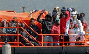 Un grupo demigrantes subsaharianos esperan para desembarcar en Gran Canaria tras ser rescatados en alta mar.