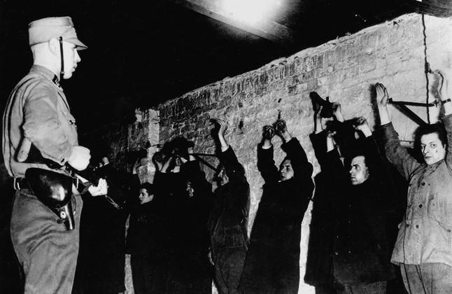 Un guardia SA amenaza a presos políticos recién llegados a los primeros campos de concentración, en 1933.