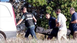 Agentes de la Guardia Civil y de los servicios funerarios trasladan el cuerpo de una mujer alemana fallecida por las fuertes lluvias del martes, en Arta.