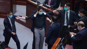 Un legislador de la oposición rodeado por agentes de seguridad del Parlamento.