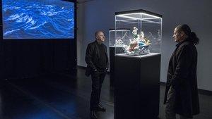 Los artistas rusos Lev Evzovich (con coleta) y Evgeny Svyatsky, con algunas de las obras que se exponen en la galería Senda.