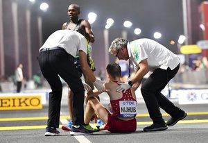Un participante del maratón necesita ayuda a la conclusión de la prueba en el Mundial de Doha.