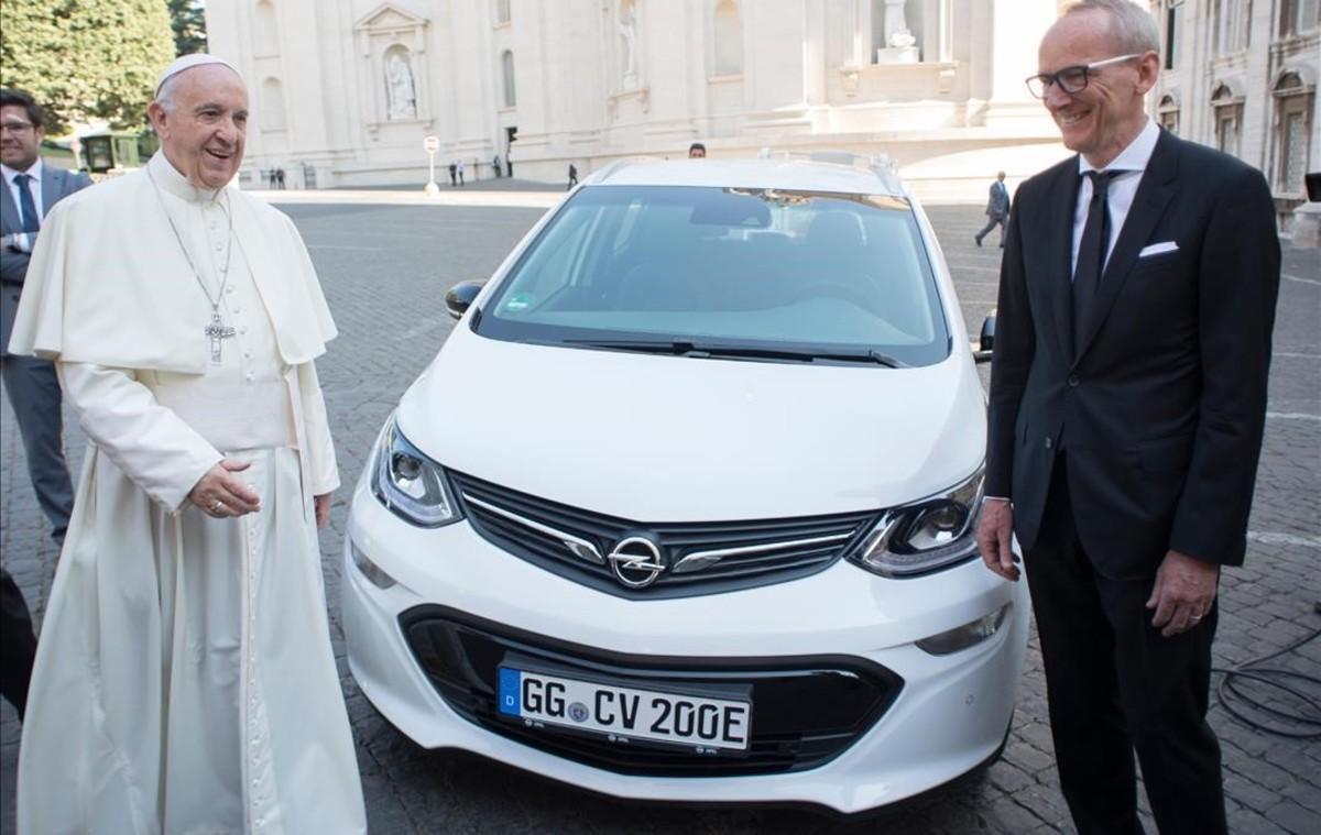 El Papa Francisco con el consejero delegado de Opel Karl-Thomas Neumann junto a un coche del modelo Ampera-e.