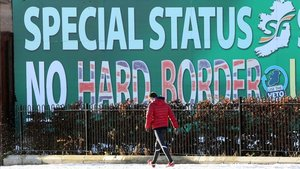 Un peatón pasa junto a un cartel en Belfast sobre el Sinn Féin rechazando una frontera dura.