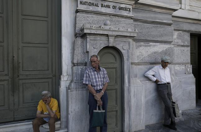 Pensionistas esperan para cobrar frente a un banco de Atenas (Grecia).