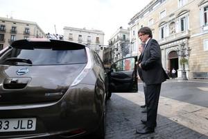 El president de la Generalitat junto al coche eléctrico con el que se ha dirigido a la Generalitat