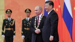 El presidente chino Xi Jinping estrecha la mano de Vladímir Putin, después de imponerle la Medalla de la Amistad durante una ceremonia en Pekín.