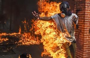 Un manifestante entre llamas después de estallar el depósito de la moto de un policía durante una protesta contra el presidente Maduro en Caracas.