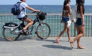 Un turista con una bicicleta eléctrica, en el paseo Marítimo de la Barceloneta.