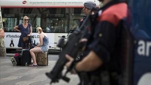 Turistas en la Rambla frente a varios agentes de los Mossos.