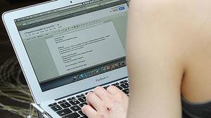 Una mujer consulta su correo electrónico en su portátil.
