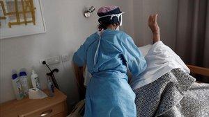 Una auxiliar atiende a un anciano de una residencia de mayores.