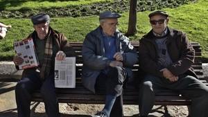 Un grupo de personas mayores sentadas en un banco de un parque.