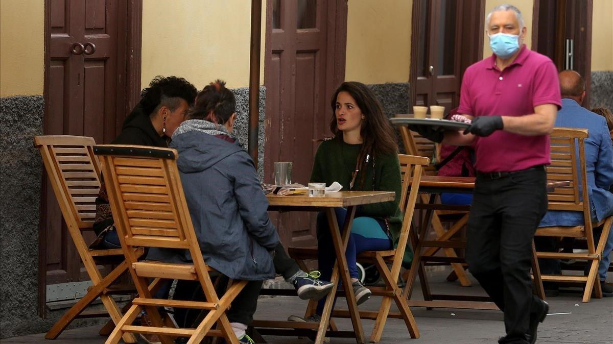 Varios clientes disfrutan de un desayuno en la terraza de un bar, en La Laguna (Tenerife).