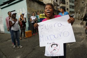 A woman with toothpaste under her nose to help with the effects of tear gas fired by security forces holds a sign that reads in Spanish  Get out Maduro   referring to Venezuelan President Nicolas Maduro  in the Cotiza neighborhood of Caracas  Security forces have fired tear gas against protesters in a poor neighborhood near the presidential palace after an apparent uprising by a national guard unit   AP Photo Ariana Cubillos