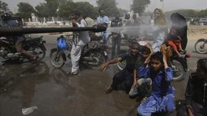 Voluntarios pulverizan a la gente en Karachi.