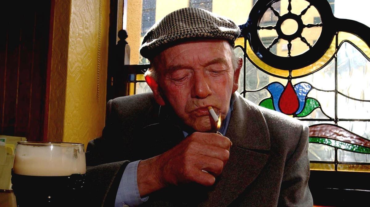 Un hombre enciende un cigarrillo en un pub de Irlanda, en el 2004.