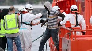 Voluntarios de la Cruz Roja ayudan a desembarcar a las 152 personas llegadas en cayuco al puerto deArguineguín, en Gran Canaria.