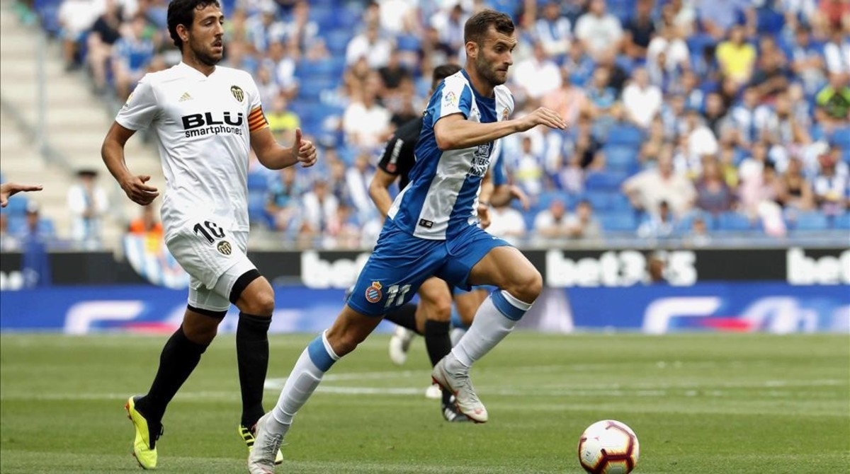 Leo Baptistao conduce el balón ante la mirada de Parejo.