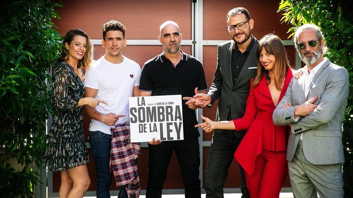Dani de la Torre, a la derecha de Luís Tosar, que sostiene el cartel de la película, junto a Michelle Jenner (de rojo) y otrosactores de 'La sombra de la ley'.