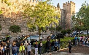 Un grupo de personas ve desfilar a la comitiva de Obama al llegar a los Alcázares.