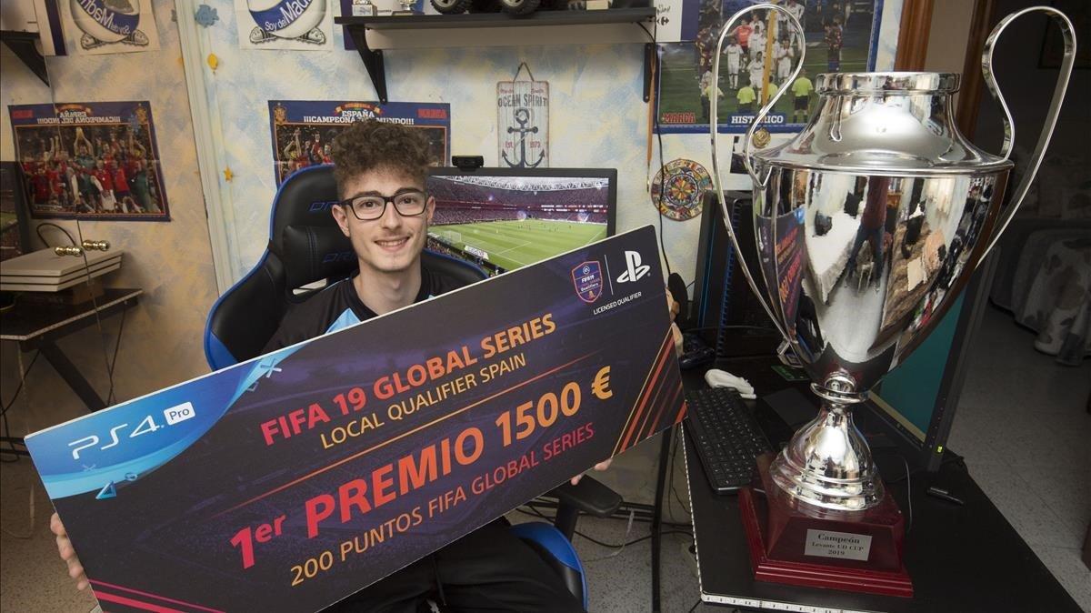 Andoni Payo, junto a su último trofeo obtenido en julio por el club de fútbol Levante Unión Deportiva, mientrasmuestra el cartel de ganador del FIFA19 Global Series en España.