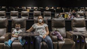 Espectadores con mascarilla, este lunes, en una sala de los Cinesa de València.