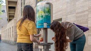 Dos chicas rellenan una botella con agua con gas en una fuente de París. Se pueden encontrar diez con burbujas.