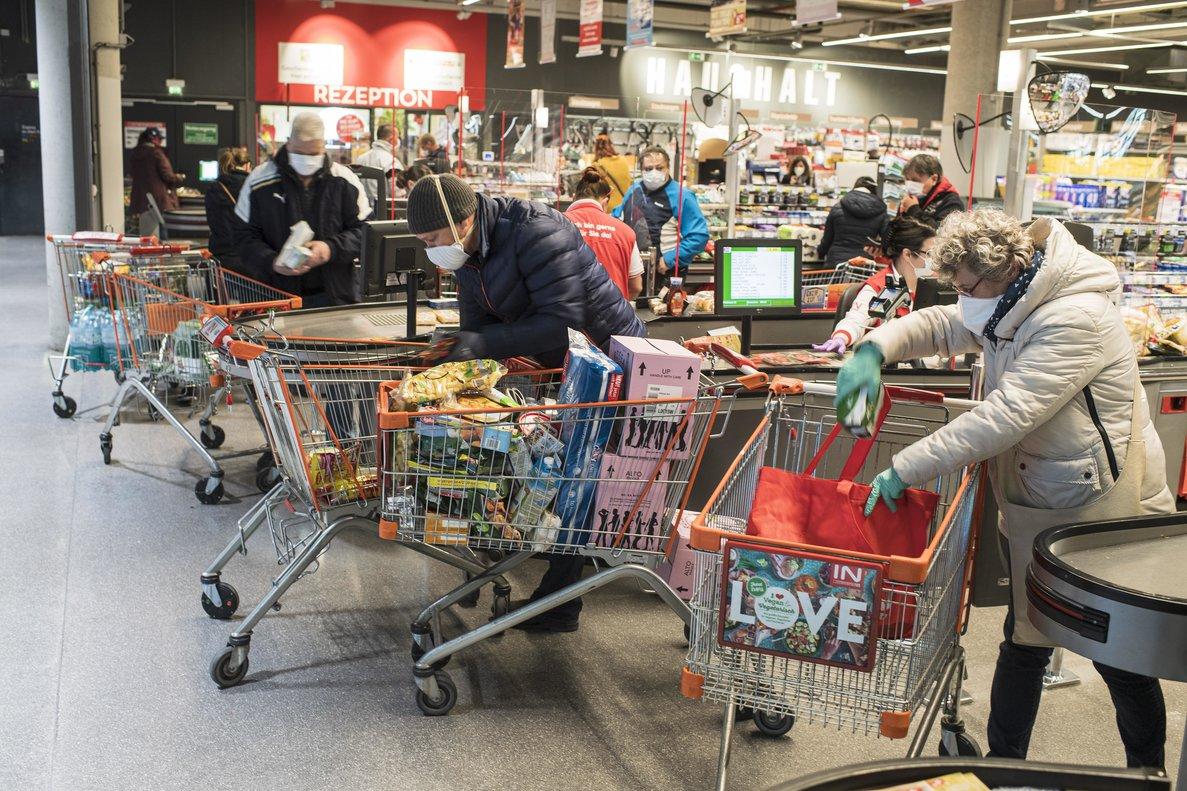 Ciudadanos hacen la compra con mascarillas en Viena.