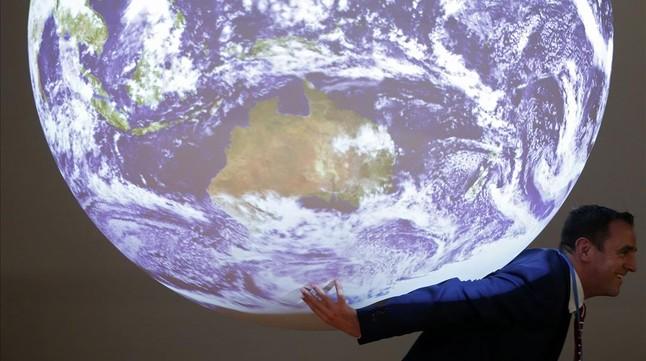 Un participant en la cimera del clima, davant de la bola del món que sexhibeix en la trobada.
