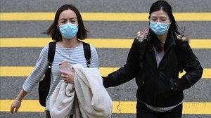 Dos mujeres con máscara, como prevención frente al brote de coronavirus, en Hong Kong.