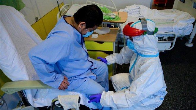 Un fisioterapeuta atiende a un paciente con coronavirus en el Hospital Puerta de Hierro de Madrid.