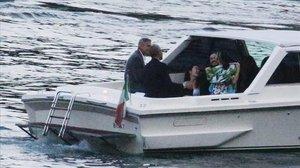 El matrimonio Clooney y la familia Obama llegan en lanchaal muelle donde se encuentra la espectacular mansióndel actor y la abogada.