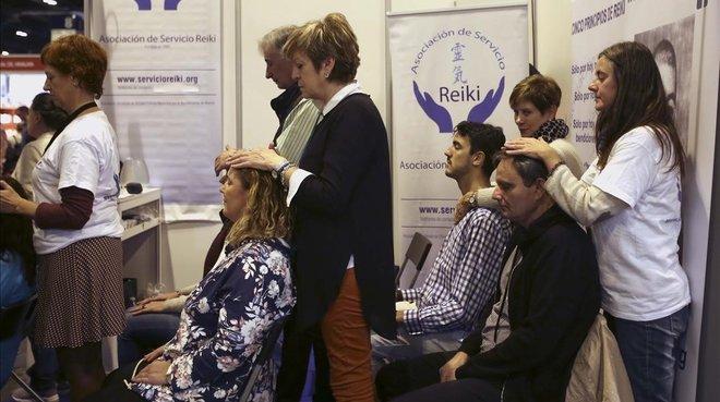 Un grupo de personas se somenten a una sesión de Reiki, considerada una seudoterapia, en el parque ferial de Madrid.
