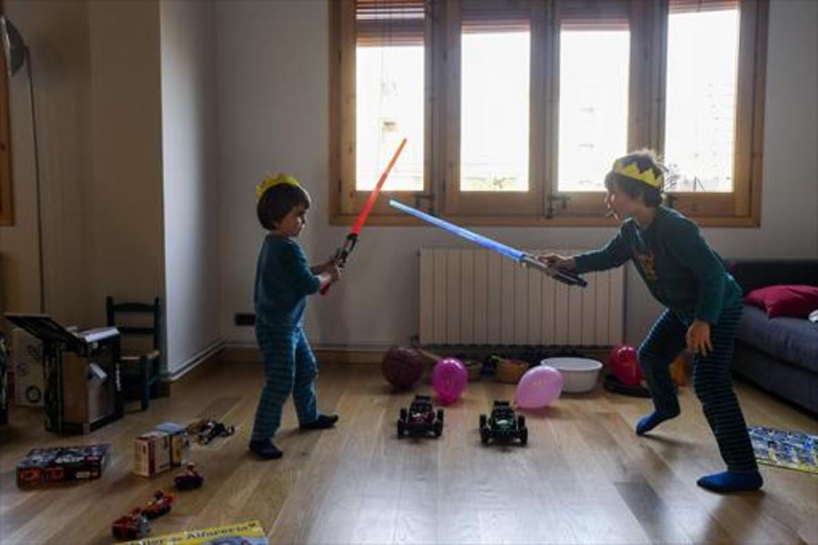 Los jedis Miquel y Mateu estrenan sus espadas láser en su piso de Barcelona, este sábado.