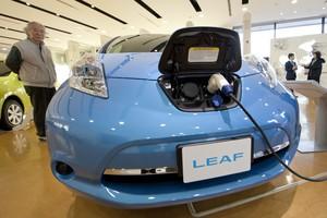Un hombre observa un coche eléctrico del modelo Leaf, de Nissan, en la fábrica de la compañía en Oppama (Japón).