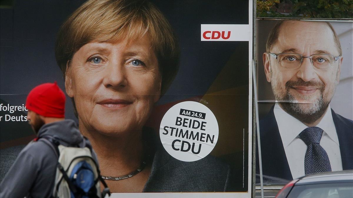 Un hombre pasa por delante de carteles electorales con los rostros de Angela Merkel y Martin Schulz, en Fráncfort.