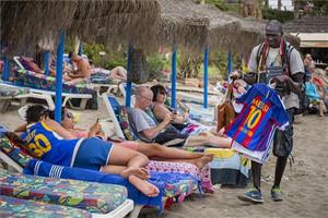 Un joven vende camisetas de Messi en la playa de Benalmádena (Málaga).