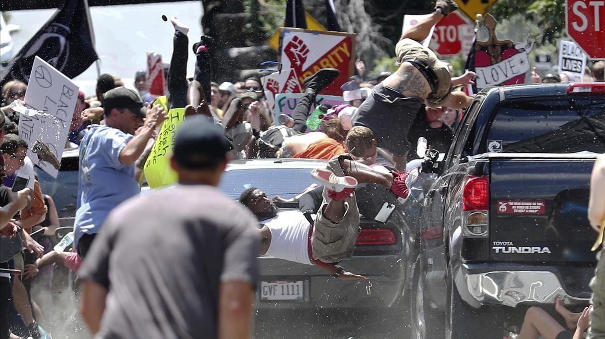 Manifestantes vuelan por losaires cuando un vehículo arrolla a un grupo que se manifiestaban en contra de losblancos-nacionalistas en Charlottesville.