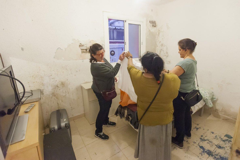 Las voluntarias Pili y Yolanda muestran ropa a Josefa Amaya.