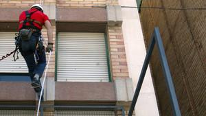 Medidas de seguridad laboral de un trabajador en una fachada.