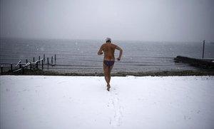 Un nadador corre hacia el mar en una playa cubierta de nieve en la ciudad griega de Tesalónica.