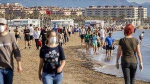 Cientos de ciudadanos dan un paseo por la playa de la Malvarrosa en Valencia.