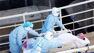 Médicos militares reciben a un paciente para ser atendido en un hospital en China, a 1 de febrero de 2020.