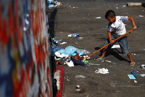 A boy sweeps rubbish at Martyrs' Square after last night protests following Tuesday's blast, in Beirut, Lebanon August 9, 2020. REUTERS/Hannah McKay