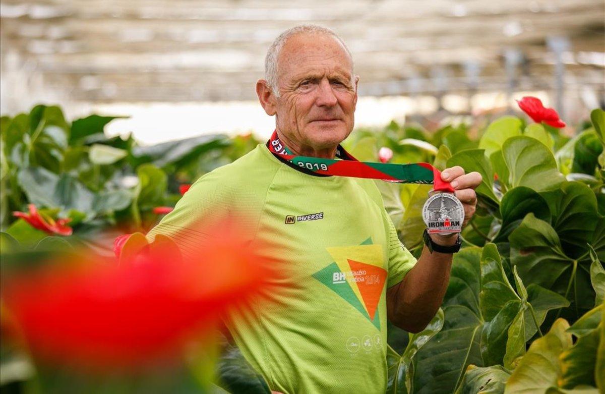 Toni Noé muestra la medalla del Ironman rodeado de flores.