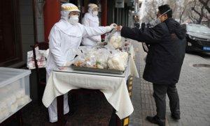 Un trabajador de un restaurante, vestido con ropa protectora, entrega a un cliente su menú, en una calle de Pekín.
