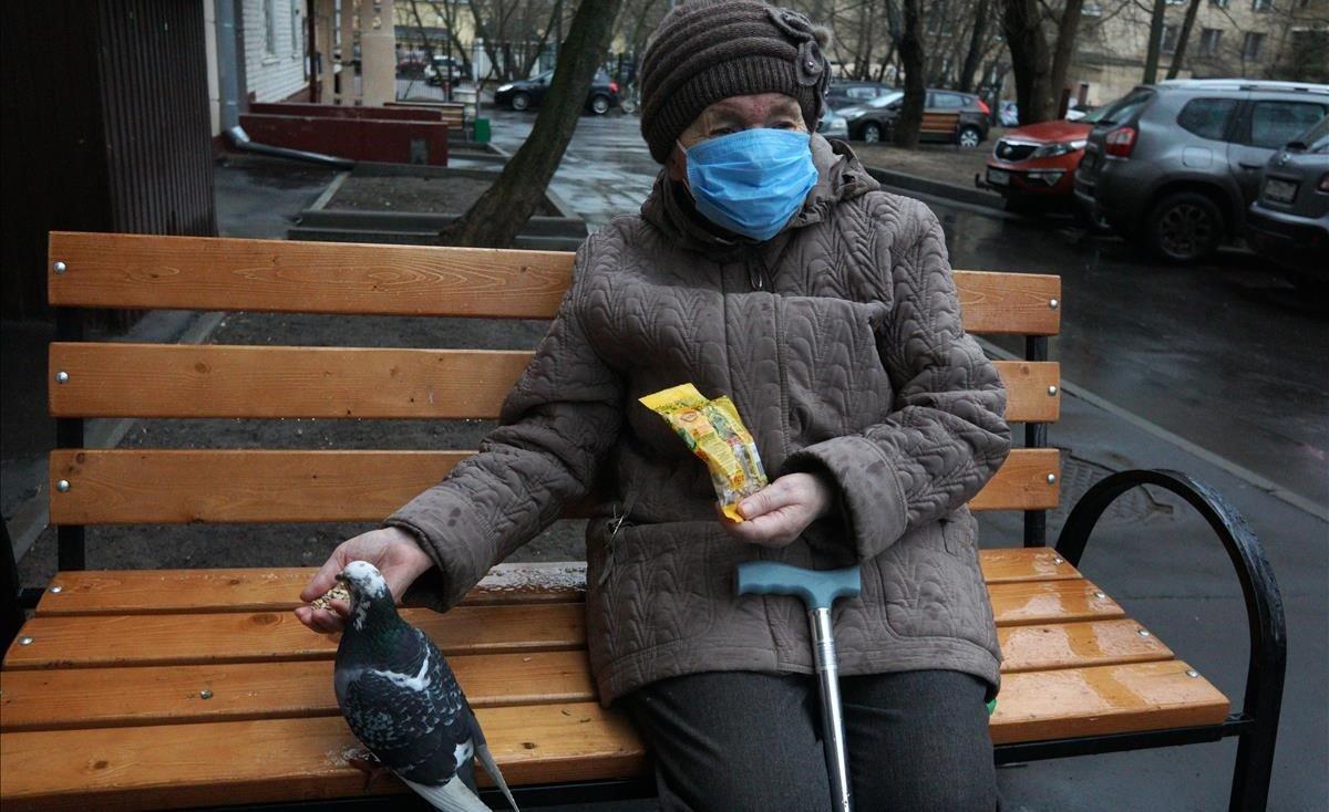Una anciana protegida con mascarilla alimenta a una paloma en un banco cercano a su domicilio, en Moscú.